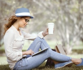 Sitting on the grass relaxing girl using laptop Stock Photo