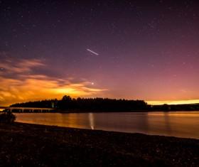 Starry sky above serene lake landscape Stock Photo