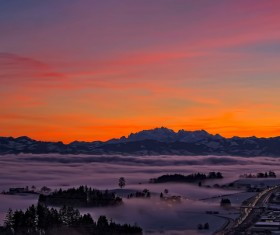 Thick fog covering mountain town at dusk Stock Photo