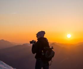 Tourist enjoying frozen mountain scene at dusk Stock Photo