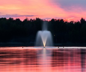 Water fountain on calm lake at dusk Stock Photo