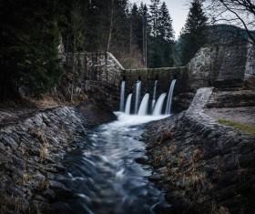 Waterfall on stone dike Stock Photo