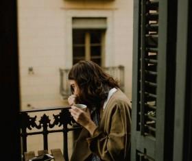 Woman drinking coffee on balcony Stock Photo