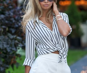 Woman in dress striped shirt wearing sunglasses Stock Photo