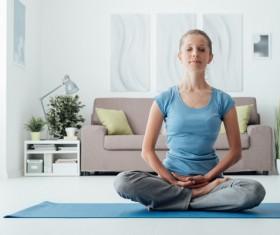 Woman sitting meditation indoors Stock Photo