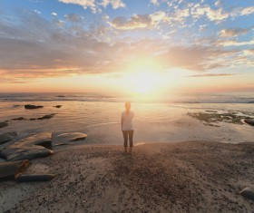 Woman standing on the beach watching the sunrise Stock Photo