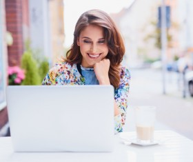 Woman using laptop in open-air coffee house Stock Photo 02