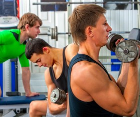 Young man doing arm exercise in gym Stock Photo
