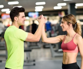 Young men and women shaking hands in gym Stock Photo