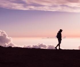 backpacker walking on mountain scene Stock Photo