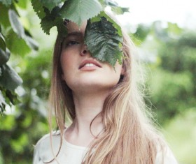 blonde woman posing with leaf hiding face Stock Photo