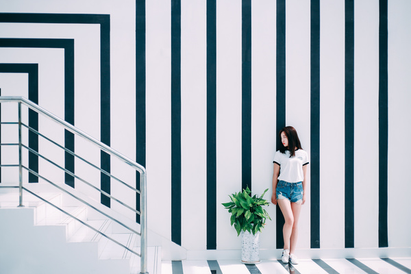 Attractive young girl posing near stripes wall Stock Photo