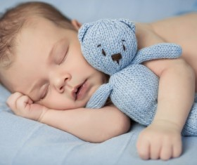 Baby holding knitted bear sleeping Stock Photo 01
