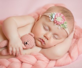 Baby holding knitted bear sleeping Stock Photo 02