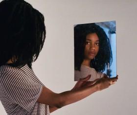 Black young girl posing via mirror Stock Photo