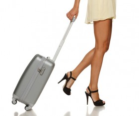Close-up of woman legs pulling a suitcase Stock Photo