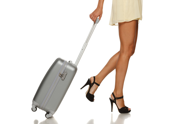 Close up of woman legs pulling a suitcase Stock Photo