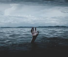 Drowning man waving hands Stock Photo