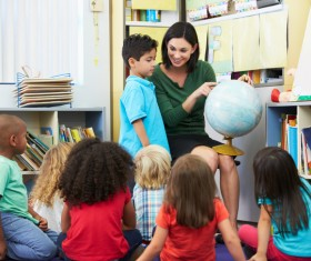 Elementary pupils listen to teacher lectures Stock Photo