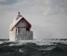 Frozen lighthouse on wavy beach Stock Photo