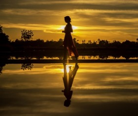 Girl walking in the sunset Stock Photo