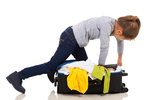 Little girl arranging suitcase clothes Stock Photo