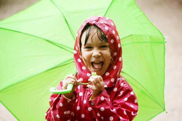 Little girl holding an umbrella on a rainy day Stock Photo