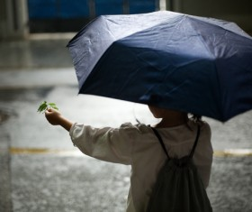 Little girl playing outdoors on rainy day Stock Photo 02