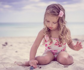 Little girl playing with sand on the beach Stock Photo