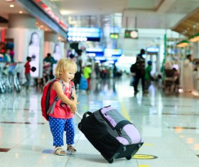 Little girl pulling luggage at the station Stock Photo