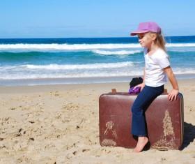 Little girl sitting on suitcase Stock Photo