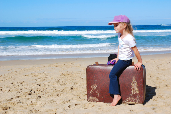 Little girl sitting on suitcase Stock Photo