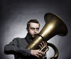 Man blowing brass instruments Stock Photo