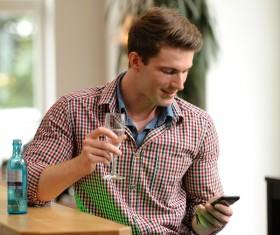 Man drinking water watching mobile phone information Stock Photo