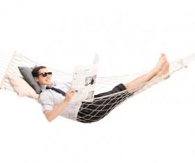 Man lying in hammock reading newspaper Stock Photo