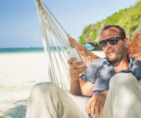 Man relaxing in hammock listening to music Stock Photo