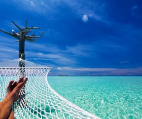 Man resting in hammock over blue sea Stock Photo