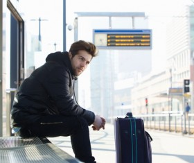 Man sitting at the station waiting for the car Stock Photo