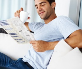 Man sitting on sofa reading morning newspaper Stock Photo