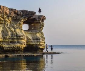 People standing on the beach rocks Stock Photo