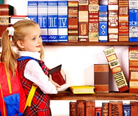 Pupil holding a heavy book Stock Photo