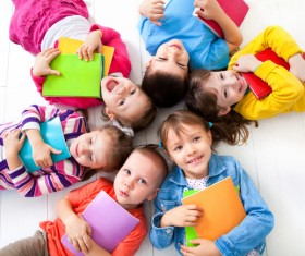 Pupils holding books lying on the floor Stock Photo