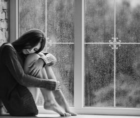 Rainy days sitting on the windowsill girl Stock Photo