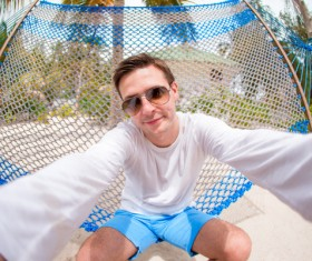 Sitting on hammock men selfie Stock Photo