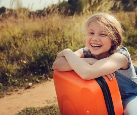 Smiling little girl and luggage Stock Photo