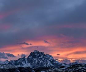 Snowy rocky mountain peak at sunset Stock Photo