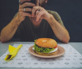 The use of smart phones shooting hamburger man Stock Photo