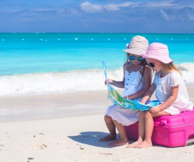 Two little girls sitting on suitcases looking at map Stock Photo