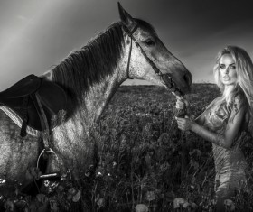 Woman and horse standing in the grass Stock Photo