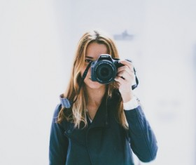 Woman holding camera to take picture Stock Photo